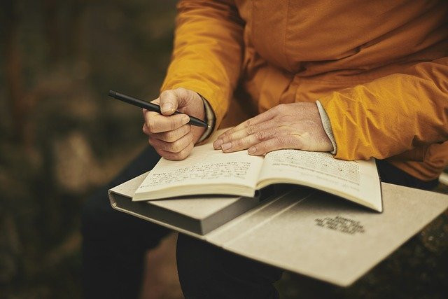 A man with a journal and pen in his hands