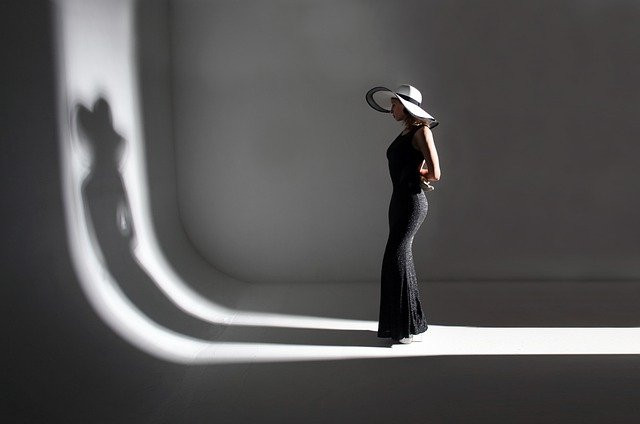 Woman with a sun hat facing her shadow