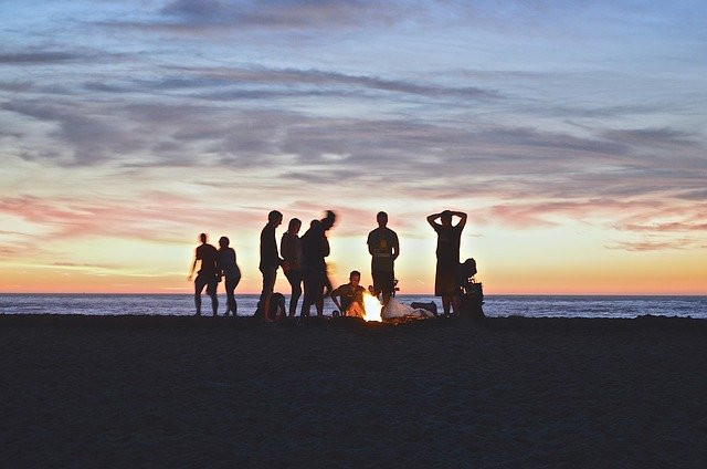 Image shows a group of people at the beach standing around a campfire at dusk.