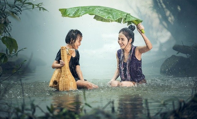Girl and lady under leaf umbrella in the rain, smiling
