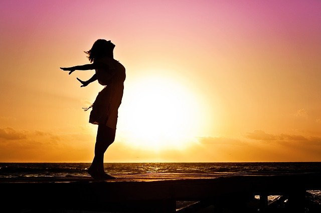 Woman silhouette in front of sunrise