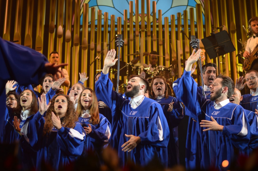 Image shows a choir group dressed in blue and white robes singing in front of an organ.