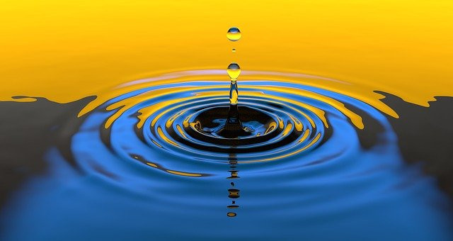 Image shows a drop falling into water and creating concentric ripples.