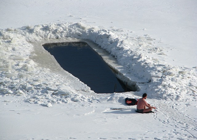 Image shows a man in shorts sitting in the snow next to a rectangular opening in the ice.