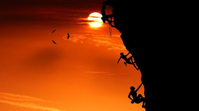 Mountain climbers under a red sky