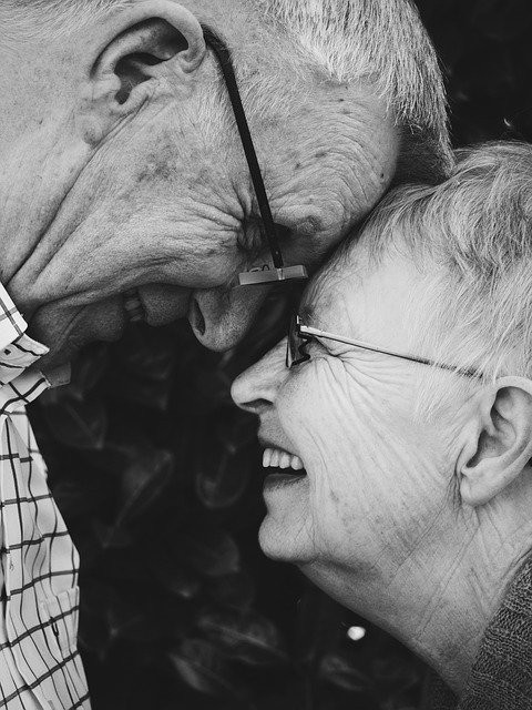Image shows a smiling elderly couple with their foreheads touching