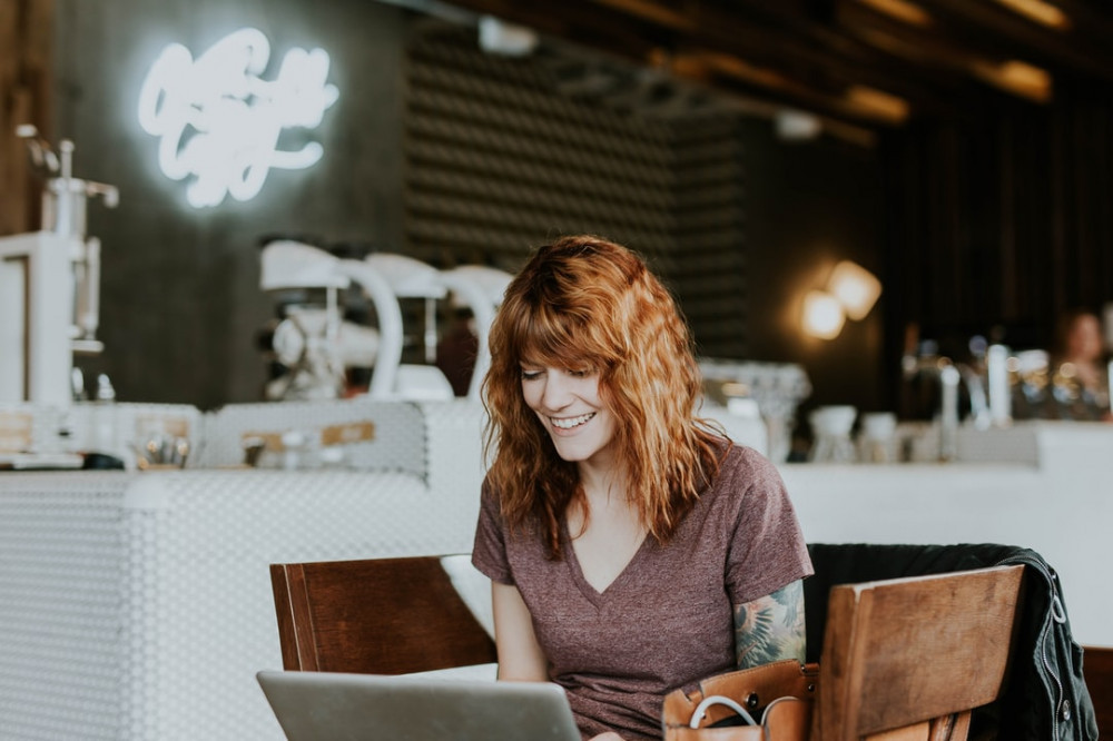 Smiling woman working on a laptop in a coffee shop