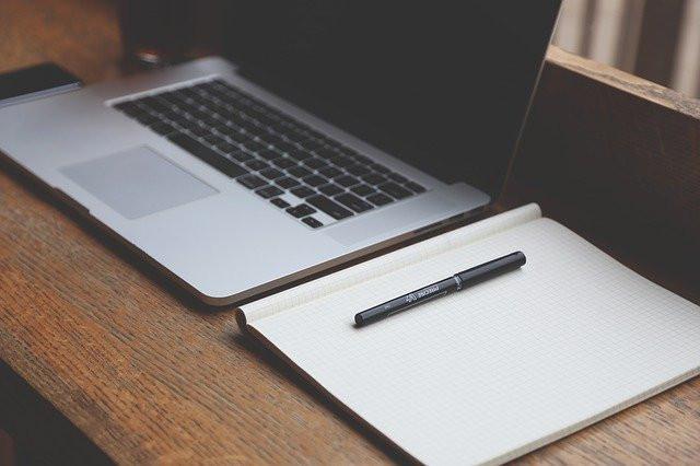 Open notebook next to a laptop