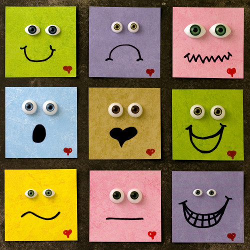 Nine colored boxes each with googly eyes and a different expression