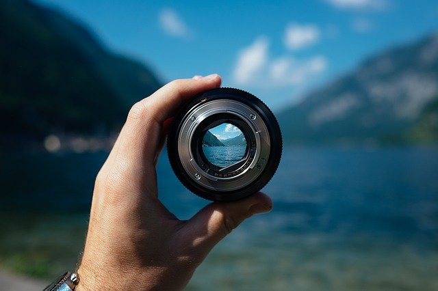 Hand holding a camera lens focused on a natural landscape