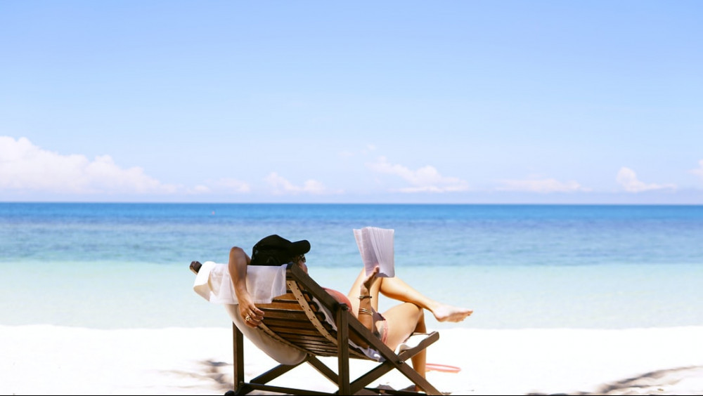 Woman relaxing on the beach reading a book