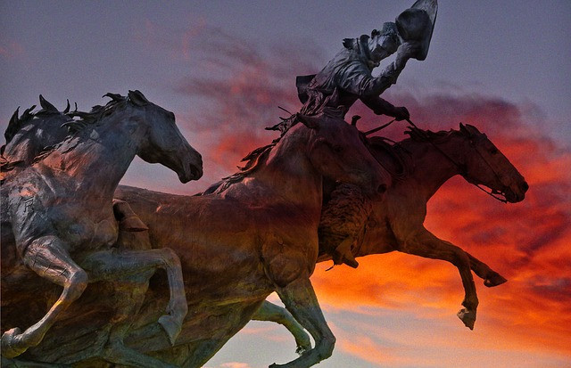 Image depicting a cowboy riding a stallion with two others following close behind in front of a cloud in orange light