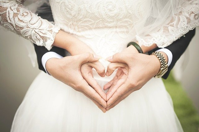 Image of a bride with her hands forming a heart over her belly and the hands of the groom wrapped around her waist, encasing her hands in his