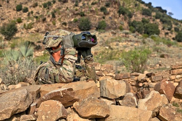 Army scout looking through binoculars