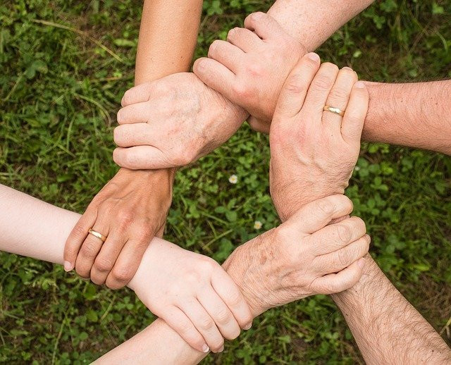 Image shows six hands holding each other to form a circle over a background of grass
