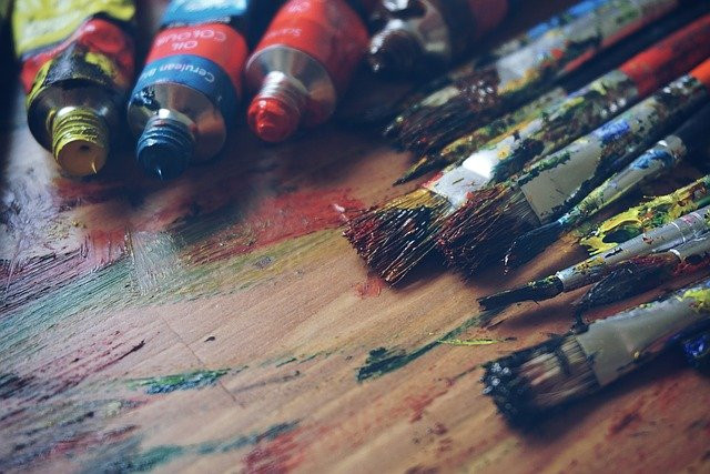 Image shows three open paint tubes and several used paintbrushes on a smudged wooden surface