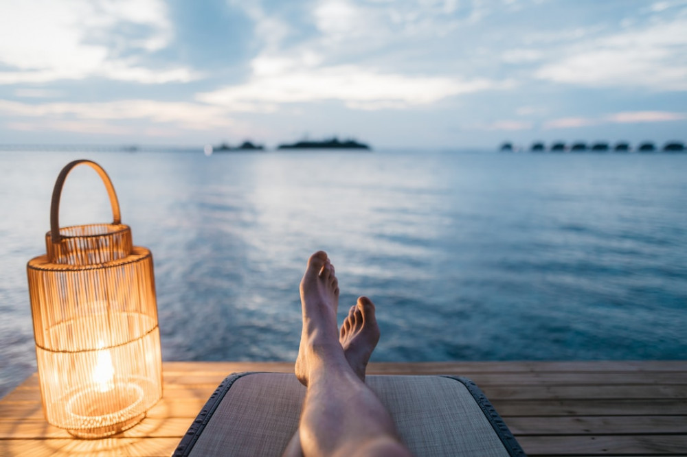 Pair of legs on a dock with a lamp next to them facing a lake