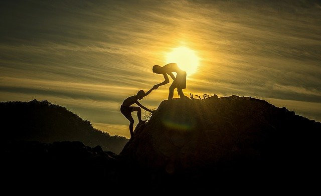 One person helping another climb a mountain with the sun in the background
