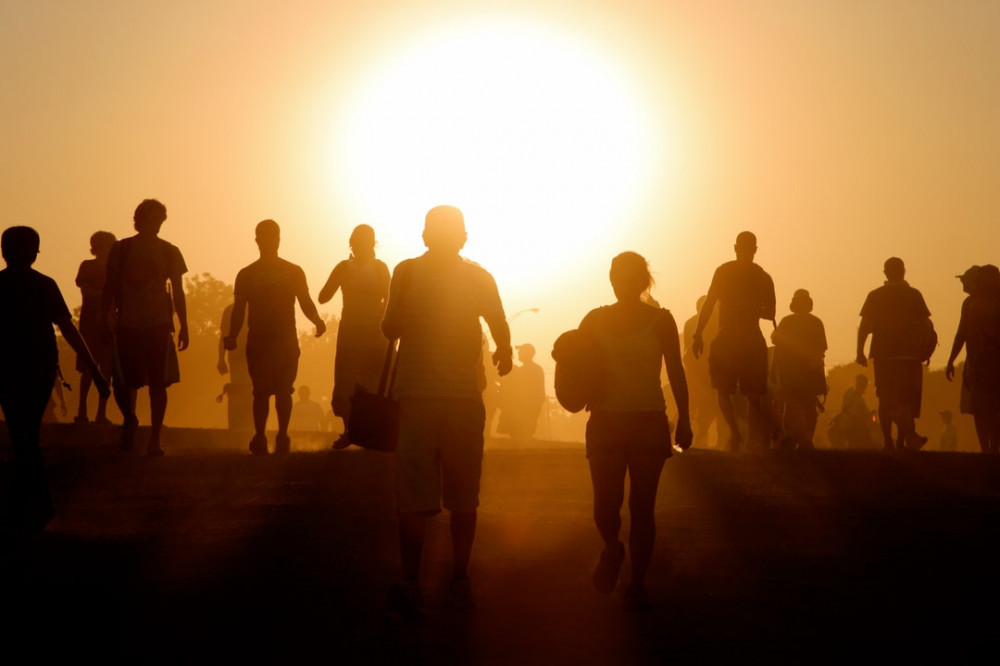 Image showing a group of people standing facing the sun