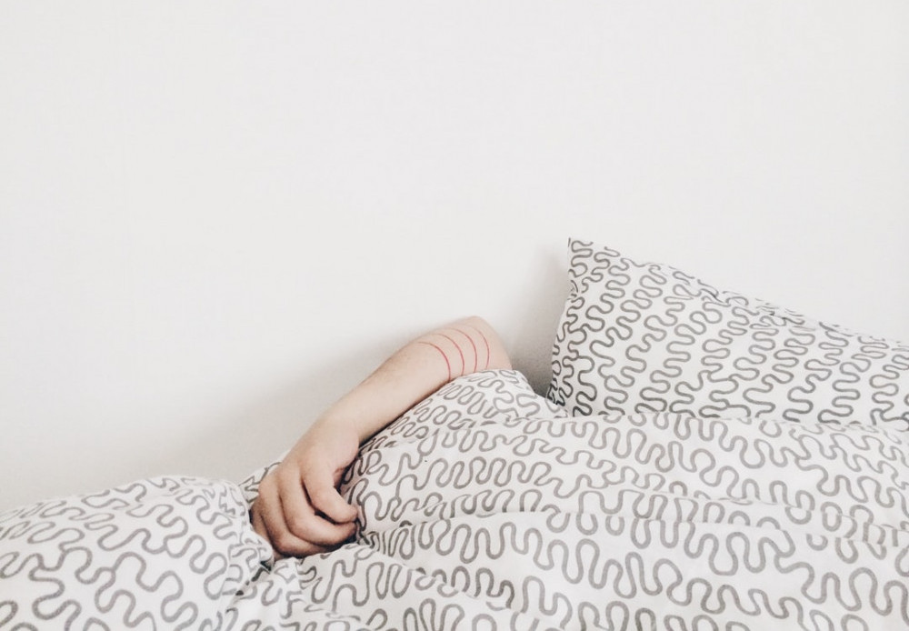 Person in bed covered by comforter