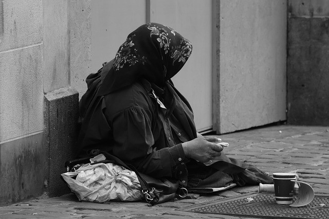 Black and white photo of a beggar sitting on the sidewalk