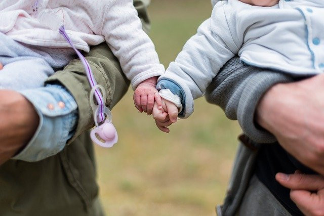 Image of two babies holding hands as they are held by two adults