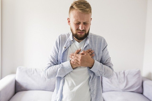 Man with an expression of pain putting his hands on his chest. A sofa is in the background