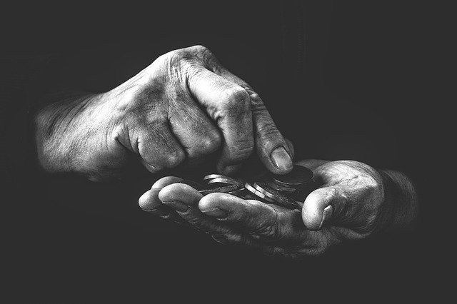Black-and-white photo showing two hands holding coins