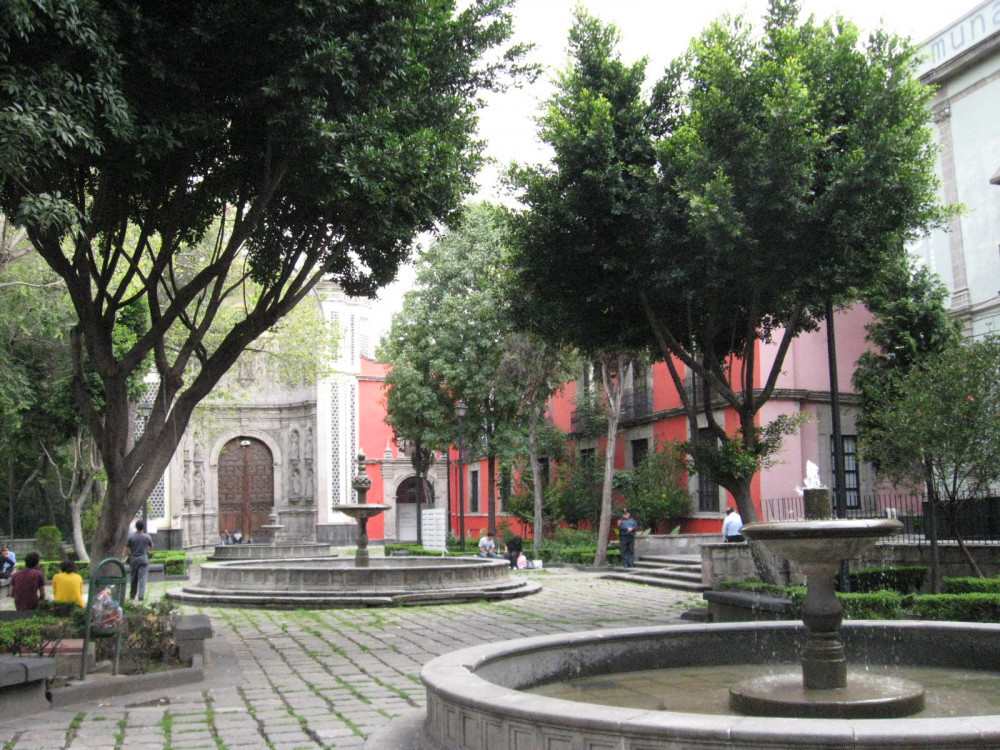 Image shows the courtyard of the Franz Mayer Museum (on right) and one of the entrances of the Parish of La Santa Vera Cruz de San Juan de Dios Church, both located on Hidalgo Street in the Centro of Mexico City just north of the Palace