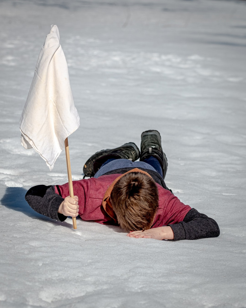 Boy lying face down in snow holding up a stick with a white flag in sign of surrender