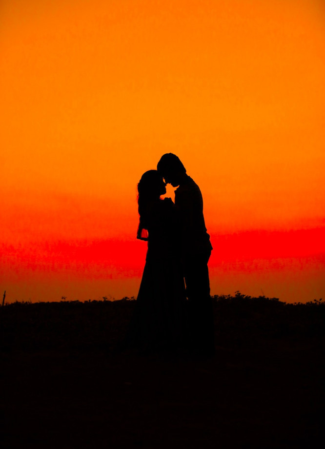 Image shows the silhouettes of two lovers in an embrace standing in front of an orange sky
