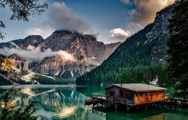 Image showing a still mountain lake with a mountain in the background and a white church. In the foreground is a wooden cabin built over the lake with a boat docked next to it.