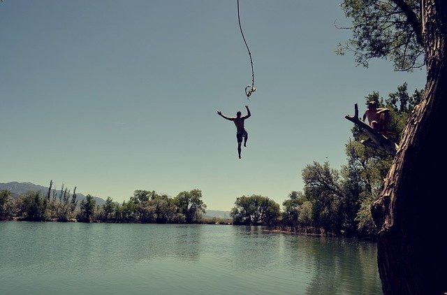 Image showing a person jumping into a lake after swinging from a rope with another person watching him from the branch of a tree