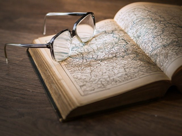 Image shows an opened book of maps with a pair of reading glasses resting on top of it