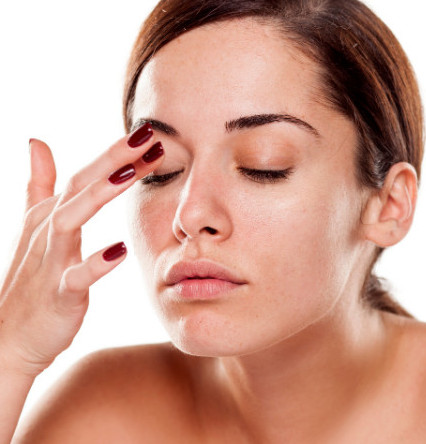 woman putting oil on her upper eyelid
