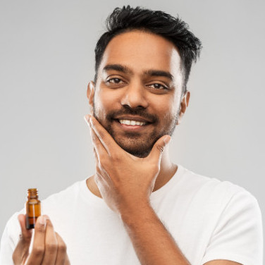 man applying oil to his beard