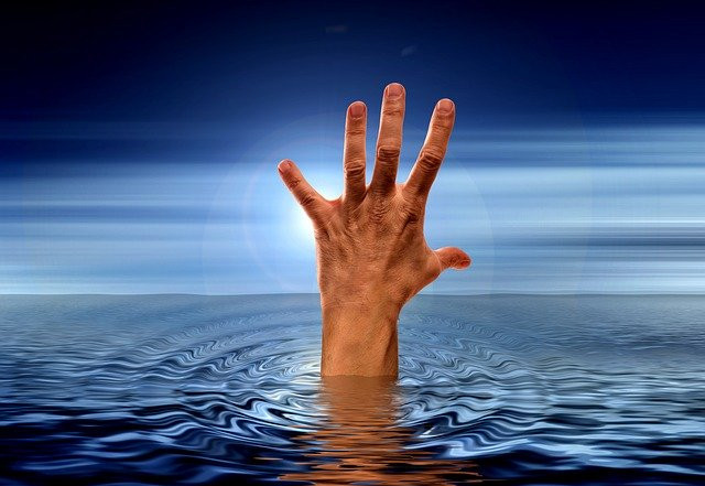 Hand reaching up from under water