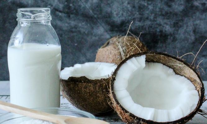 Coconut broken in half beside a bottle of milk