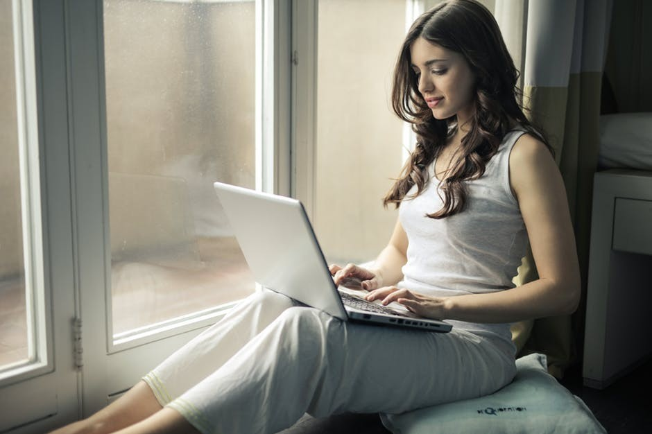 A picture of a woman sitting next to a window working on her laptop.