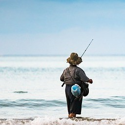 Image of woman fly fishing in ocean