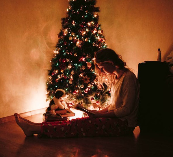 Image of woman by lighted Christmas tree