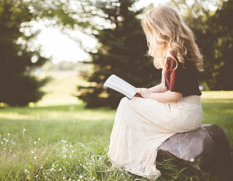 Image of woman sitting with open bible in a beautiful field.