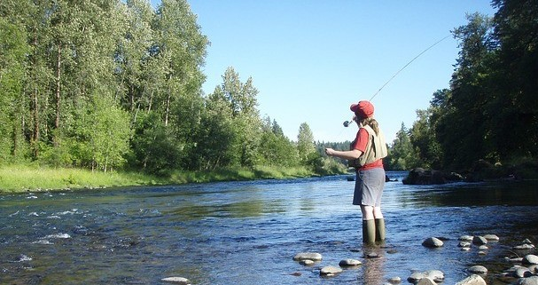 Image of woman fly fishing in stream