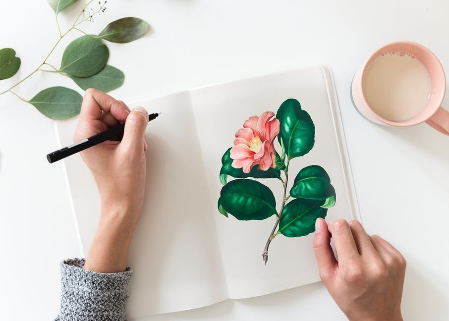 Image of artist painting a flower