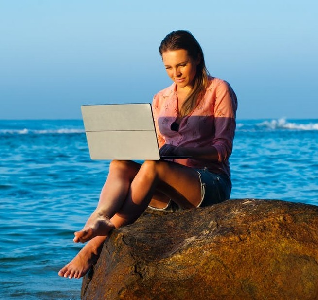 Image of young woman near ocean working on notebook computer
