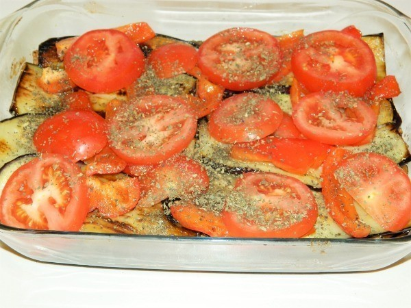 Fourth layer of moussaka is oregano seasoned sliced tomatoes and fried sweet red pepper
