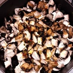 Chicken Stew With Mushrooms and Sour Cream-Chopped Mushrooms on Simmering Meat and Vegetables