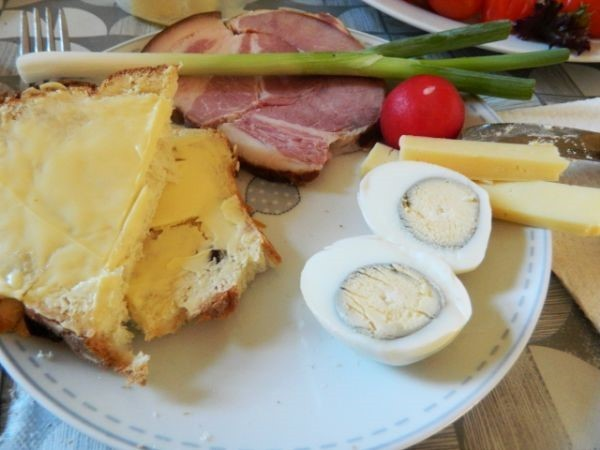 Hard-boiled eggs, smoked boiled ham, sweet bread and butter.