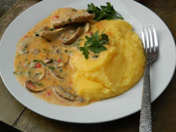 pork shoulder stew with mushrooms and sour cream served with polenta