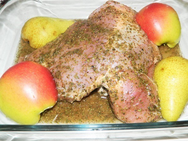 Turkey thigh in tray with apple and pear